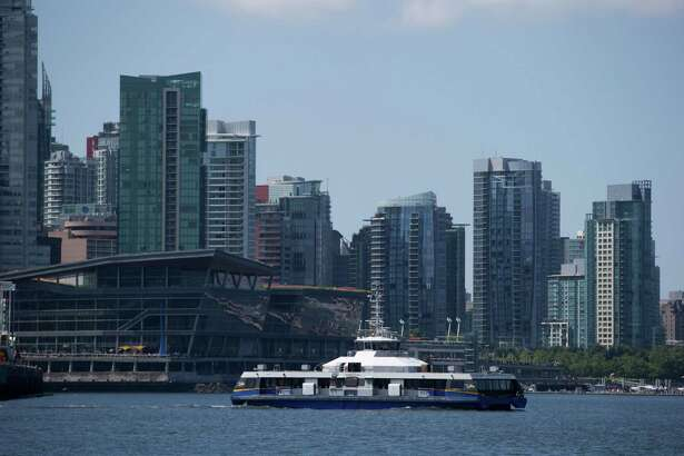 A Seabus commuter vessel travels on the harbor as condo towers are seen in the distance in Vancouver, British Columbia, on July 11, 2017.