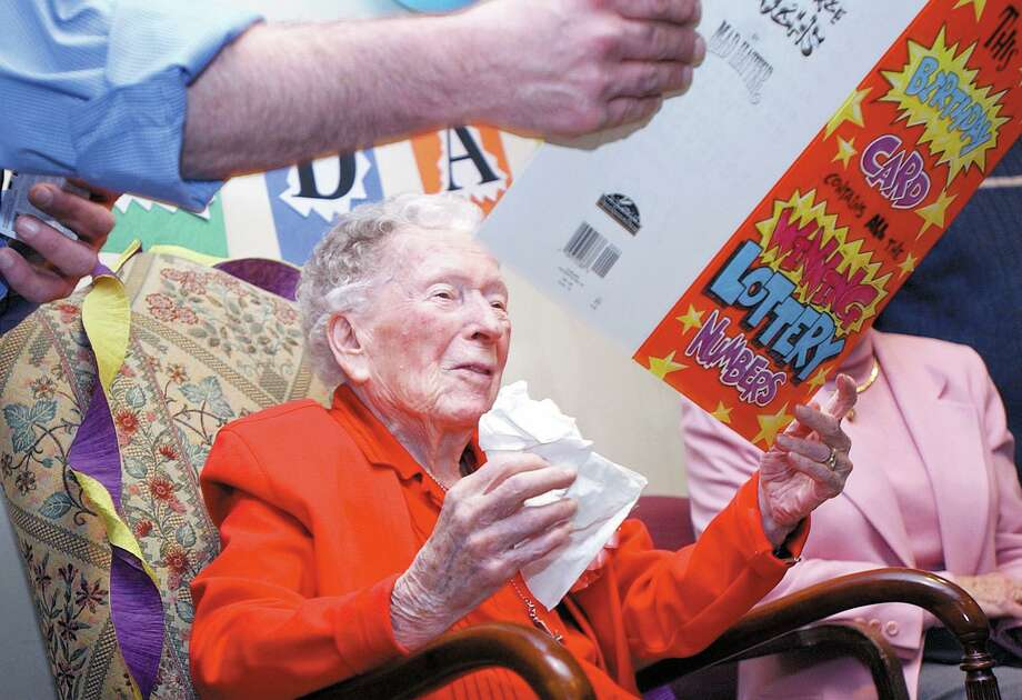 A resident looks at a card signed by most of the residents and staff at One MacDonough Place in Middletown at her 100th birthday party. Photo: Hearst Connecticut Media File Photo