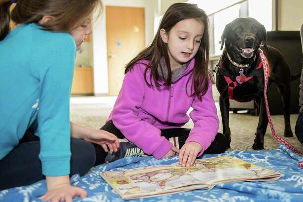 "Gabby, 7, and Olivia, 9, Baxendale of Wilton read ""Annie and the Wild Animals"" to Pepper, a rescue therapy dog from ROAR, at Wilton Library during a previous Tales for Tails program."