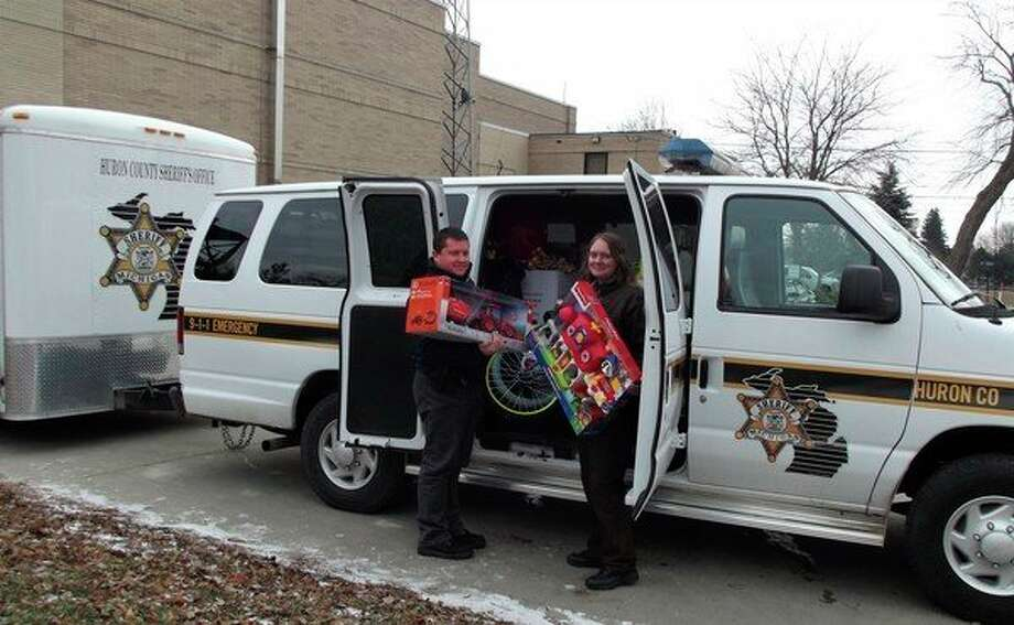 Deputies Daryl Ford and Kim Kociba load presents into an office van and trailer. They will be taken to the upcoming Toys for Tots distribution this coming Saturday morning. (Courtesy Photo)