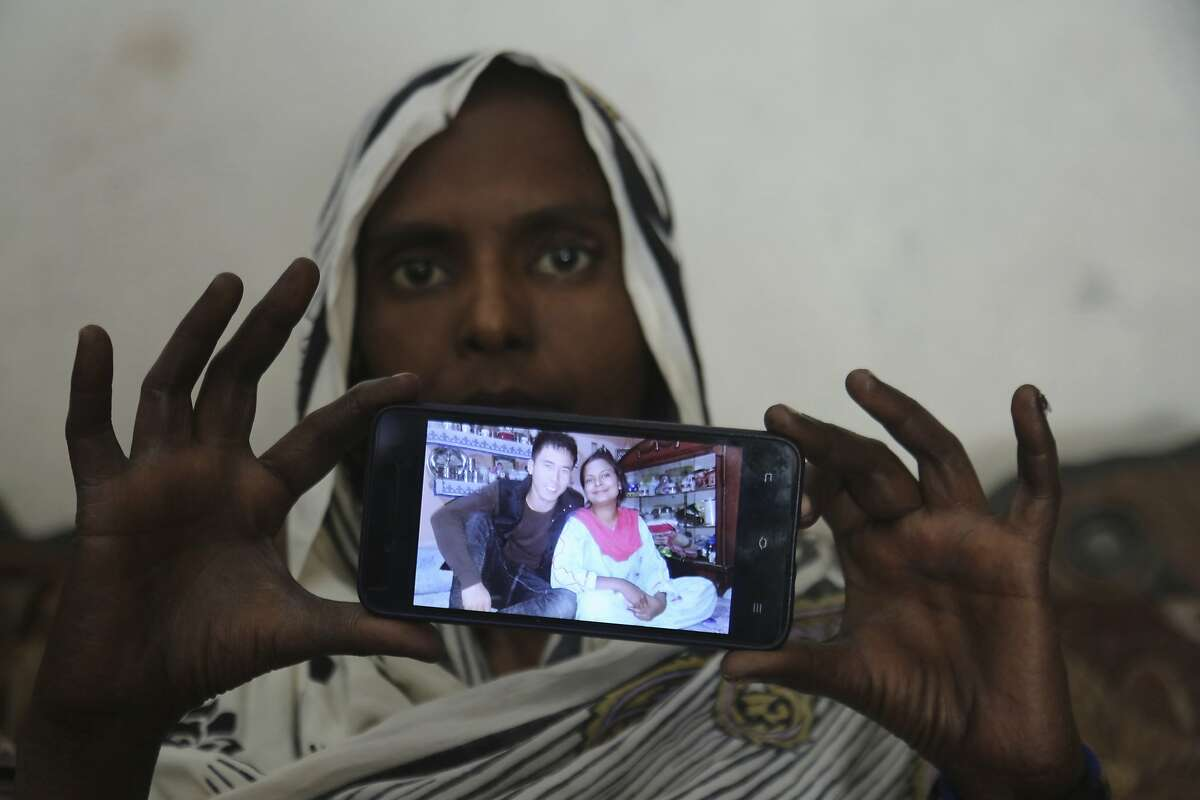 In this April 14, 2019 photo. Pakistani Christian woman Samiya David shows her picture with Chinese husband, in Gujranwala, Pakistan. Samiya had been in China just two months when her brother got a phone call telling him to pick her up at the airport. When he arrived, he found Samiya in a wheelchair, malnourished and too weak to walk, said her cousin Pervaiz Masih. She died barely five weeks later. Masih was among the relatives who prepared Samiya's grave and attended her burial in May. (AP Photo/K.M. Chaudary)