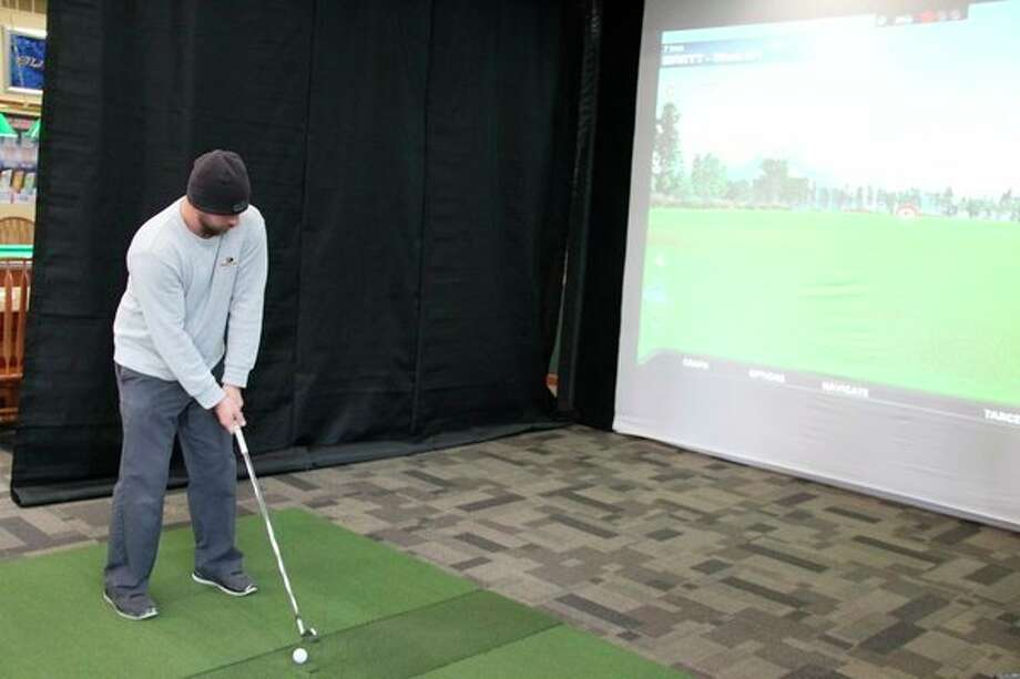 Brett McBride, the owner of Century Oaks Golf Course in Elkton, tries out the new golf simulator. It provides an 18-hole golf experience indoors. (Robert Creenan/Huron Daily Tribune)