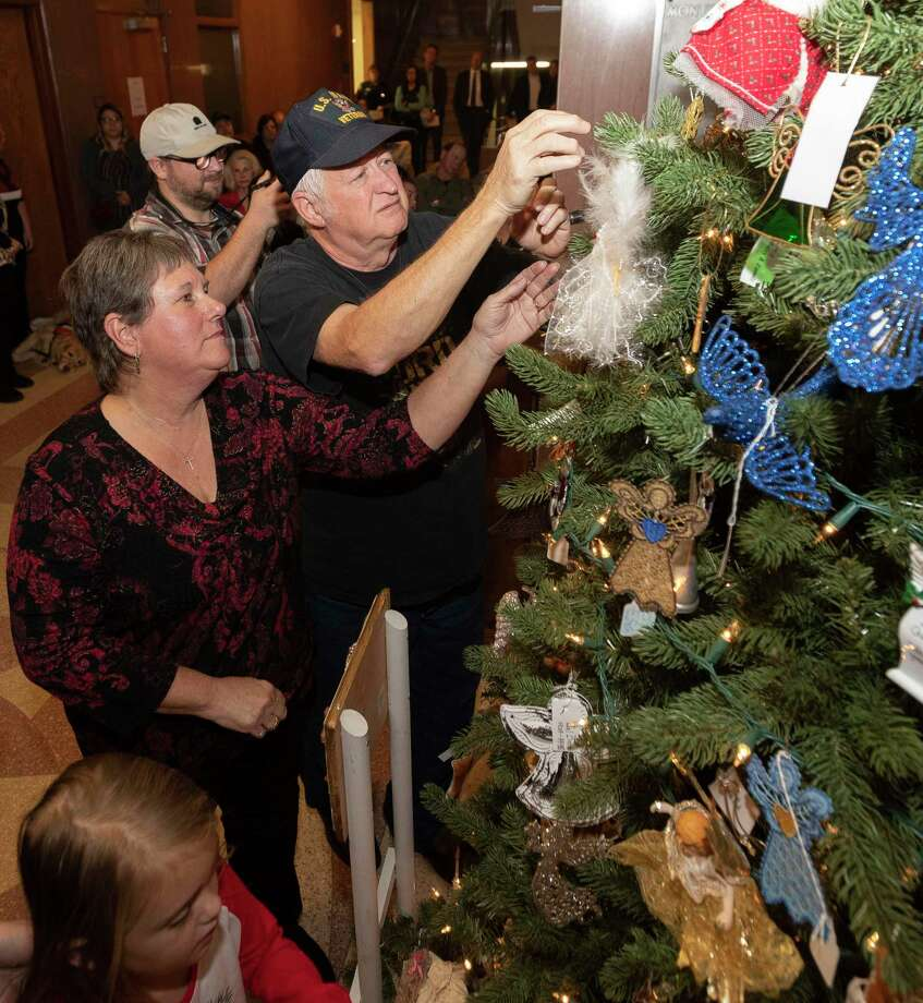 Charles Trotter hangs an ornaments beside his wife, Sandy, in memory of their daughter, Melissa, during the annual Tree of Angels dedication, Thursday, Dec. 12, 2019, in Conroe. Larry Swearingen was executed by lethal ejection in August for the 1998 death of the Trotter's daughter. The 23-year-traditon brings friends and family of victims of violent crimes together to hang personalized ornaments on a Christmas tree in the lobby of the Montgomery County Courthouse in memory to their late loved ones. Photo: Jason Fochtman, Houston Chronicle / Staff Photographer / Houston Chronicle