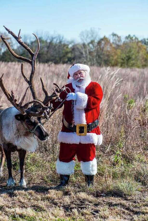 """Santa's """"cousin,"""" Steve Pegram, poses with a reindeer during a holiday photo shoot in Jersey County. Pegram tells children there's only one Santa but he has many cousins; that's why they all look similar. Photo: Photo Credit Jody Jedlicka