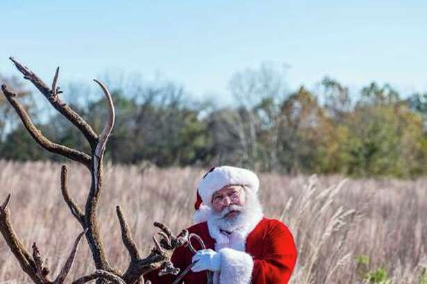 "Santa's ""cousin,"" Steve Pegram, poses with a reindeer during a holiday photo shoot in Jersey County. Pegram tells children there's only one Santa but he has many cousins; that's why they all look similar."