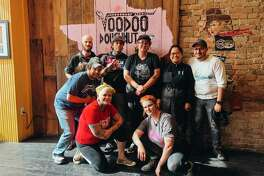 Voodoo Doughnut is looking to hire 70 employees for its new shop coming to Houston in January. Here, some Austin staff members pause from their work to take a photo.