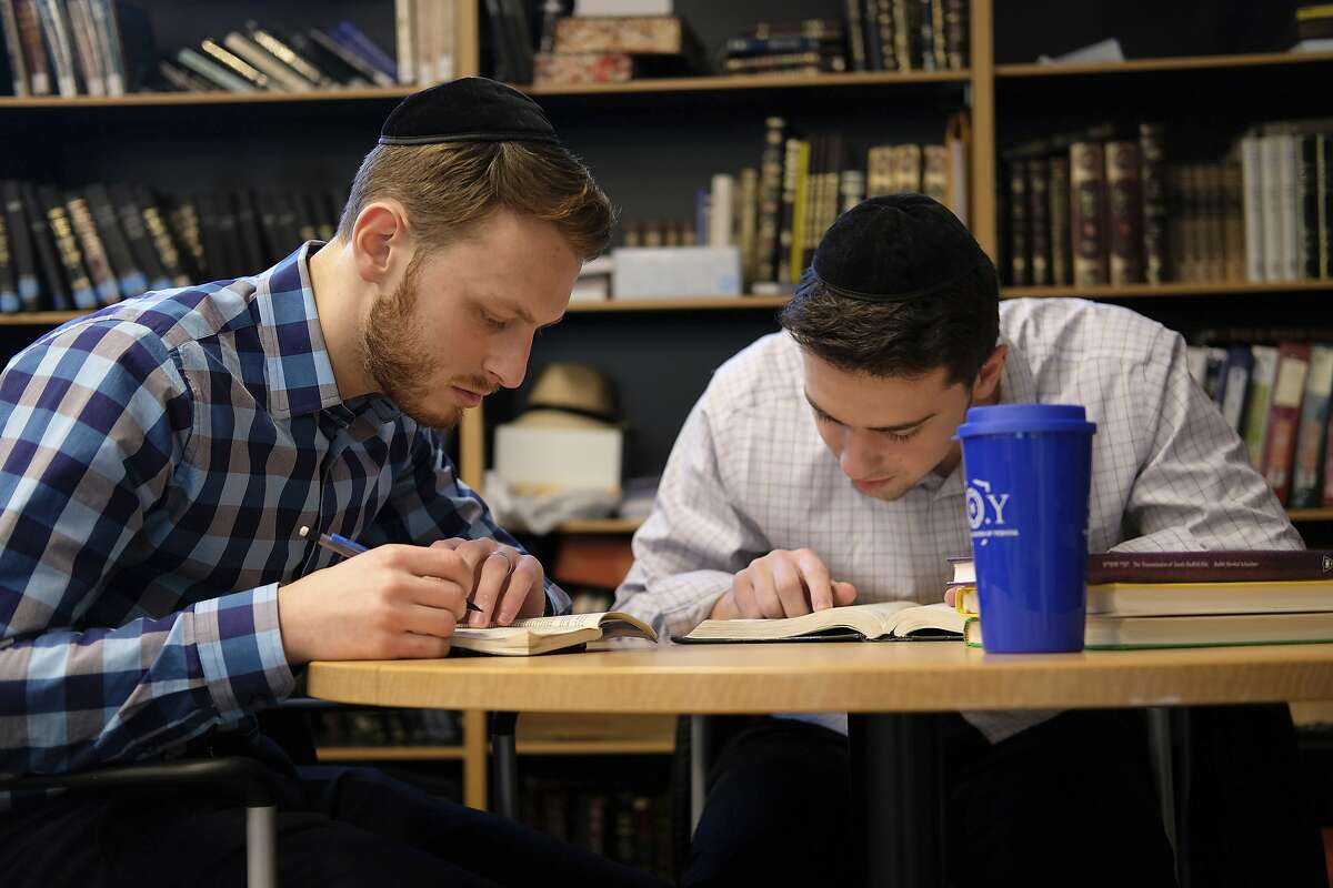 Yeshiva University students Aaron Heideman, left, and Marc Shapiro study in the university's library in New York, Thursday, Dec. 12, 2019. They praised President Donald Trump's executive order to expand the scope of potential anti-Semitism complaints on U.S. college campuses. They said they worry that friends attending other universities might be targeted by anti-Semitic attacks and that this could help protect them.