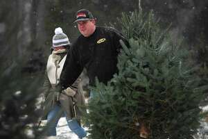 Kimberley Locke, of Danbury, and Jason Ingraham, of Oxford, brave the first snowfall of the season as they cut their own Christmas tree at Jones Family Farms in Shelton on Dec. 1. Locke, a singer, placed third in season two of American Idol.