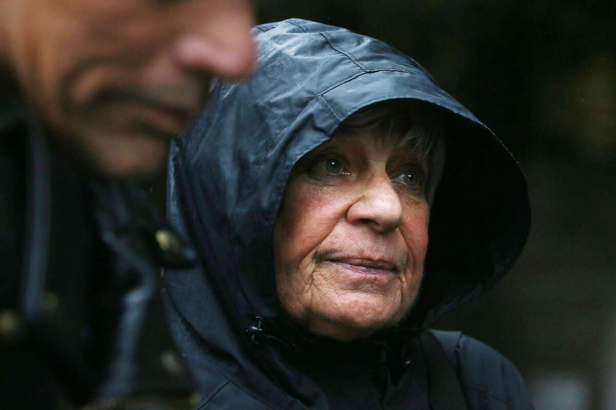KaLani Raposa (l to r), who is formerly homeless, and Kathleen Finigan, homeless activist, stand in the rain talking to a resident of the homeless encampment along the Joe Rodota Trail during a visit to the encampment on Wednesday, December 11, 2019 in Santa Rosa, Calif.