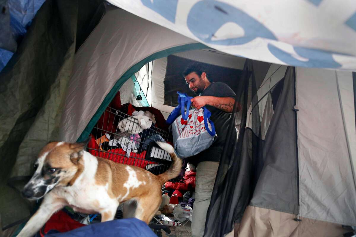 Johnathan Rosario, who lives at the homeless encampment along the Joe Rodota Trail, organizes his laundry in his tent on Wednesday, December 11, 2019 in Santa Rosa, Calif.