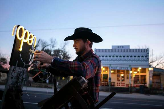"Troy Moore sets up a neon ""open"" sign outside the newly reopened dance hall in Hye before an evening of dance lessons and music."