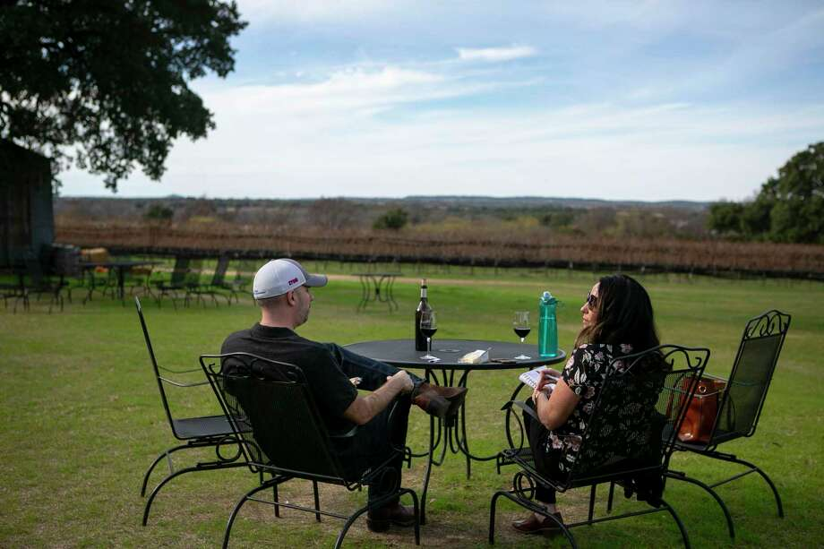 Celebrating a weekend without kids, Travis and Betsy Hensley enjoy glasses of wine as they look out on the William Chris Vineyards. Photo: Josie Norris /Staff Photographer / **MANDATORY CREDIT FOR PHOTOG AND SAN ANTONIO EXPRESS-NEWS/NO SALES/MAGS OUT/TV