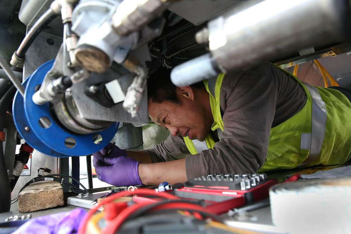 Nelson Lee, electrical transit mechanic, works on a bus to replace fans, while working in the yard at the SFMTA Potrero maintenance facility on Friday, December 13, 2019 in San Francisco, Calif.