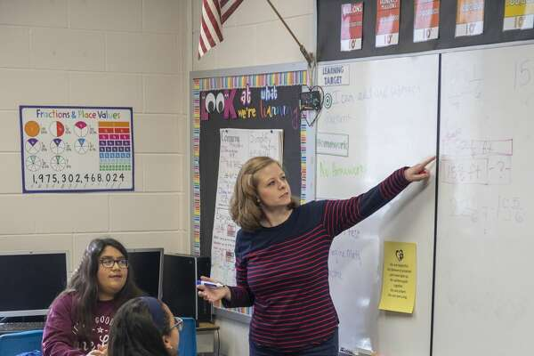 Halston McCalla a kindergarten through sixth grade math specialist shows students how to work fraction equations Friday, Dec. 13, 2019 at Long Elementary School. Jacy Lewis/Reporter-Telegram