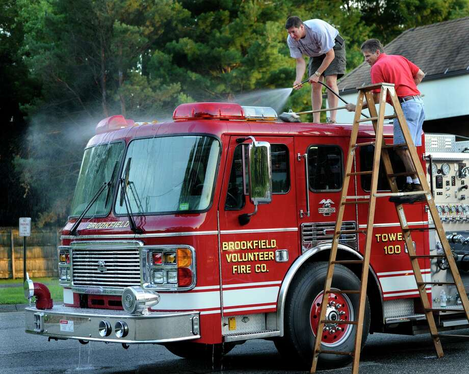 Robert Weinstein, left, and Glenn Martone, firefighters with the Brookfield Volunteer Fire Co., wash down the ladder truck Monday evening, July 30, 2012. Once a month, the company's regular meetings includes an apparatus check. Cleaning the equipment is often on the agenda. Photo: Carol Kaliff / Carol Kaliff / The News-Times
