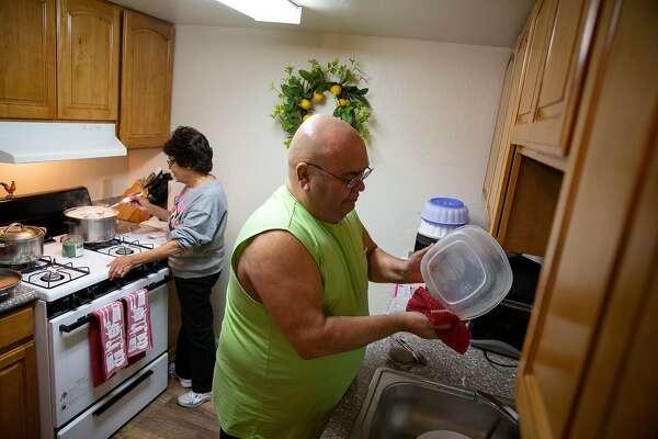 From left: Ana Lupercio cooks as Guadalupe Lupercio cleans at their apartment on Wednesday, Nov. 27, 2019, in Vacaville, Calif.