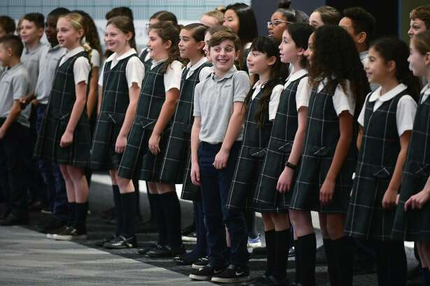 The All Saints Catholic School Choir including fifth-grader Jonathan Crataro, center, perform Christmas songs Friday, December 13, 2019, at the SoNo Collection mall in Norwalk, Conn.