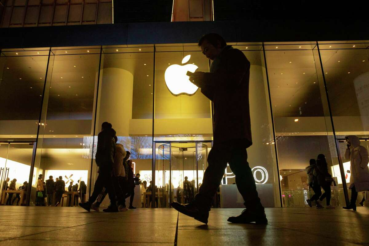 A man looks at his phone as he walks past a store of US tech giant Apple in a retail district in Beijing on Friday, Dec. 13, 2019. China deputy trade envoy says China, U.S. have reached trade deal, will reduce punitive tariffs on each other's goods (AP Photo/Ng Han Guan)