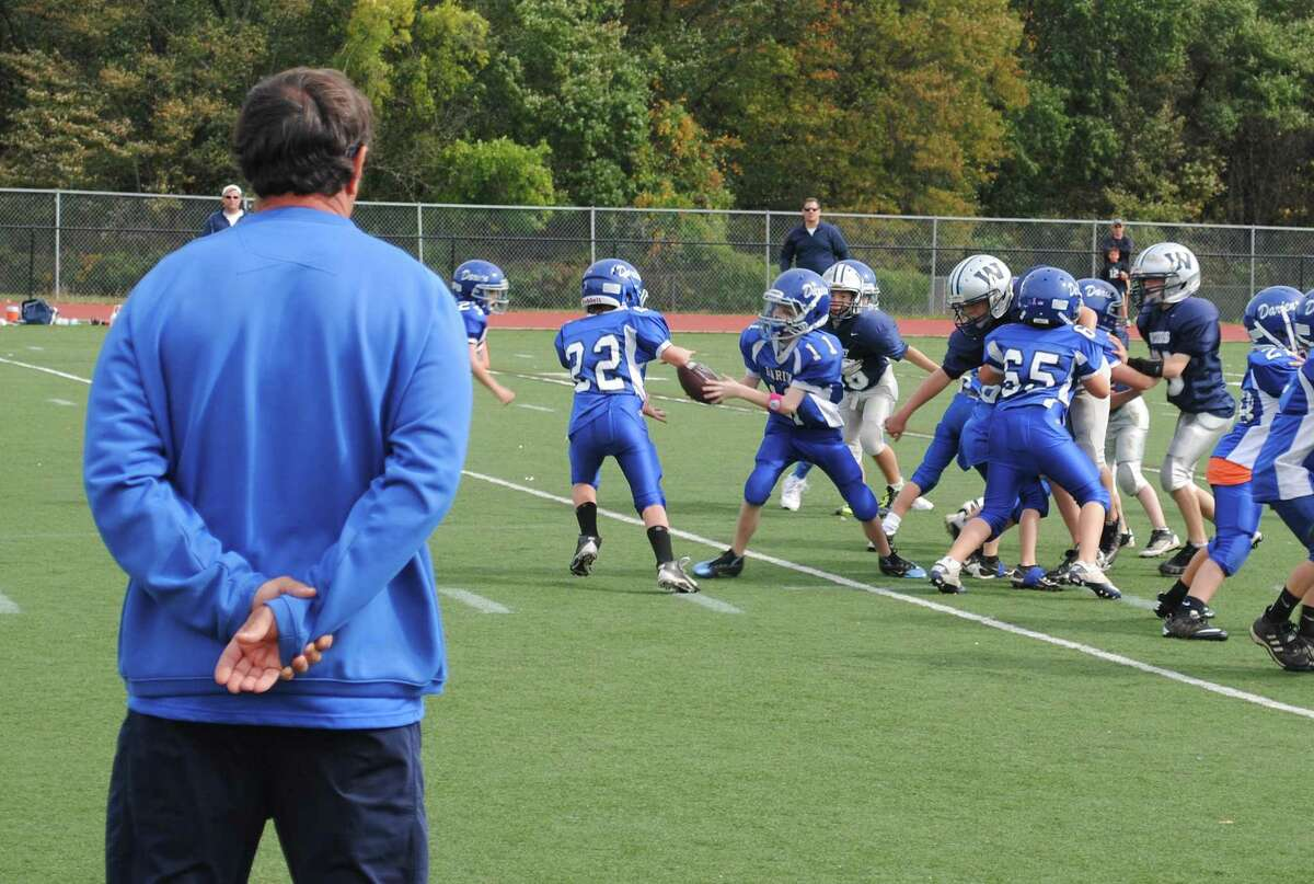 Rob Trifone watches the Darien Junior Football League third-grade team during a game in 2010. Trifone has coached that group of players for the past 10 seasons, and many are seniors on his 2019 Blue Wave varsity team.