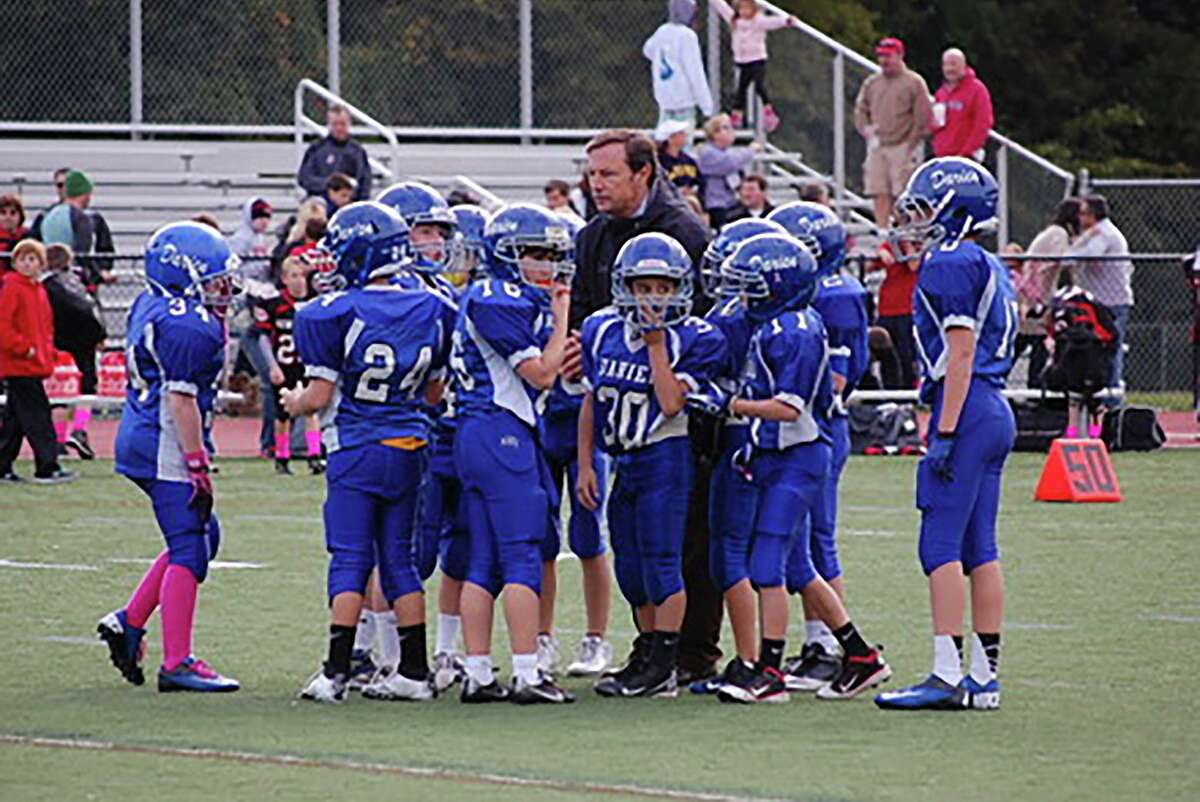 Darien High School football coach Rob Trifone in the huddle with the Darien Junior Football League's third grade team during the 2010 season. Trifone has coached that group of players for the past 10 seasons, and many are seniors on his 2019 Blue Wave varsity team.