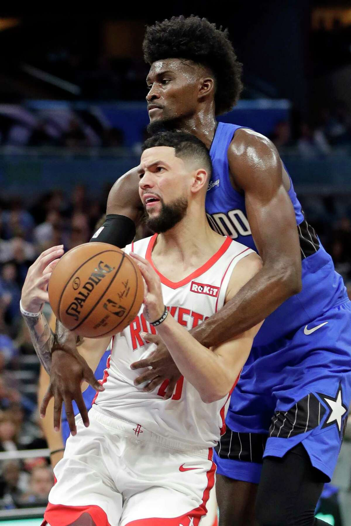 Orlando Magic's Jonathan Isaac, right, fouls Houston Rockets' Austin Rivers as he goes to the basket during the first half of an NBA basketball game, Friday, Dec. 13, 2019, in Orlando, Fla. (AP Photo/John Raoux)