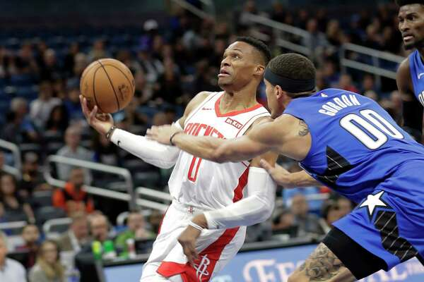 Houston Rockets' Russell Westbrook, left, goes to the basket past Orlando Magic forward Aaron Gordon (00) during the first half of an NBA basketball game, Friday, Dec. 13, 2019, in Orlando, Fla. (AP Photo/John Raoux)