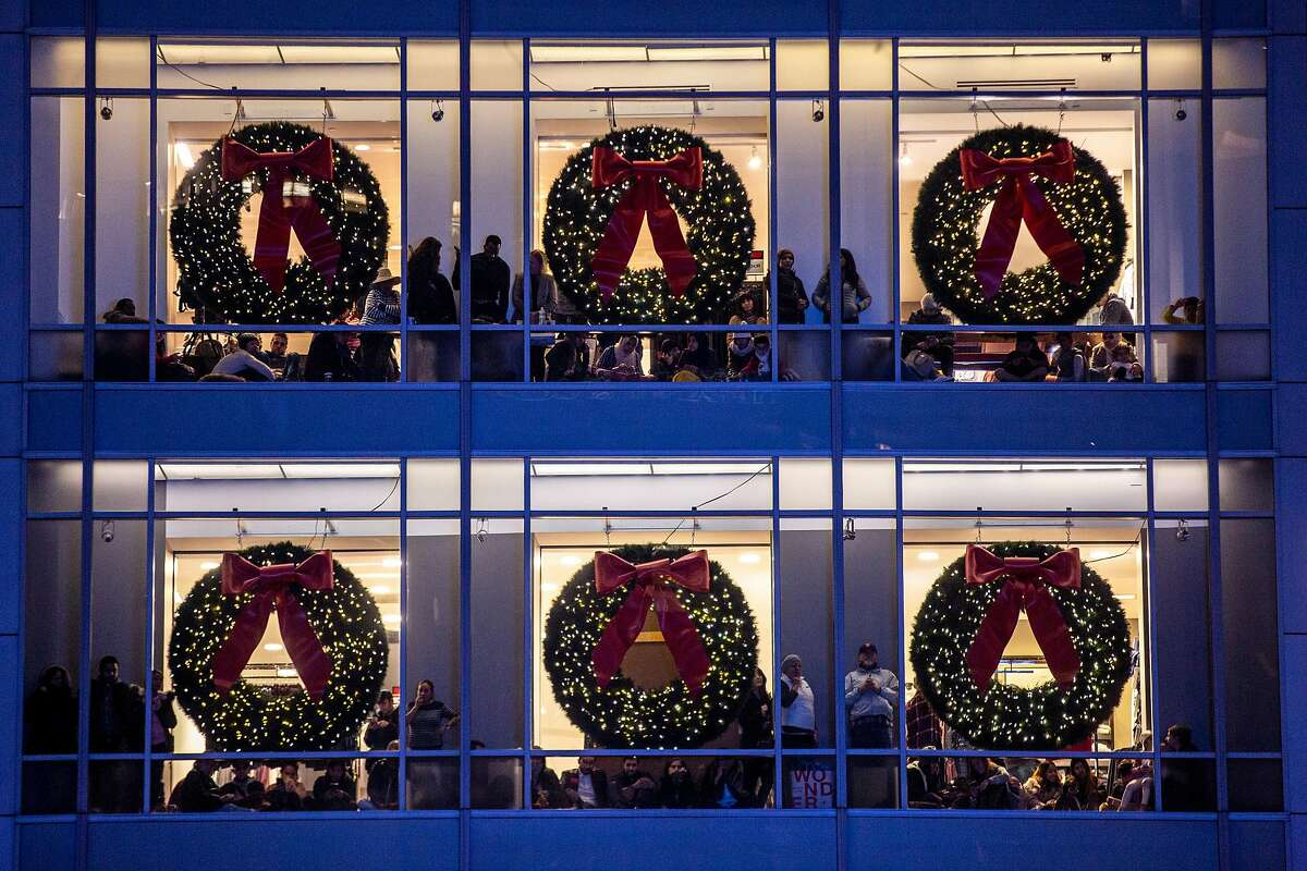 People gather at the top floors of Macy�s at Union Square for the Christmas tree lighting ceremony on Friday, Nov. 29, 2019, in San Francisco, Calif.