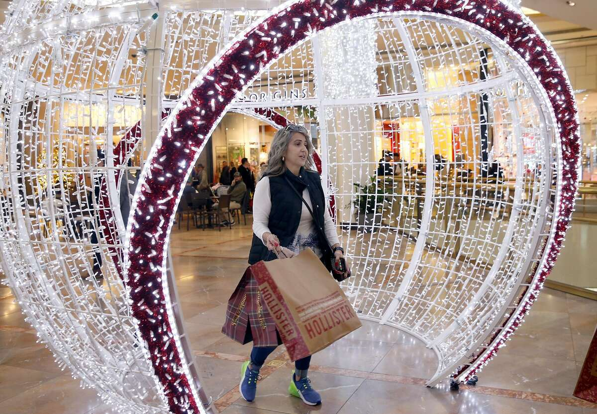 Christine Pereira walks through a holiday display while shopping on Black Friday at the Westfield SF Centre mall in San Francisco, Calif. on Nov. 29, 2019.