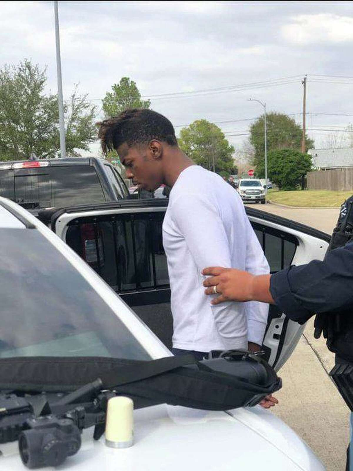 Harris County sheriff's deputies escort Tavores Henderson, alleged murderer of Nassau Bay Police Sgt. Kaila Sullivan, into a car after a two-day manhunt.