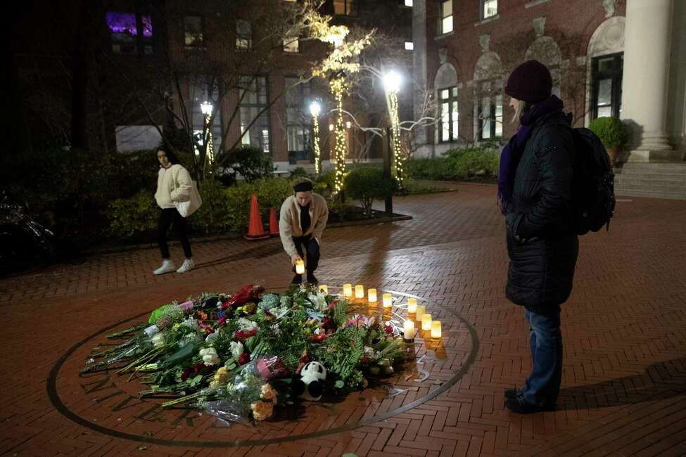 People pause and place a candle at a make-shift memorial for Tessa Majors inside the Barnard campus, Thursday, Dec. 12, 2019, in New York. Majors, a 18-year-old Barnard College freshman from Virginia, was fatally stabbed in a park near the school's campus in New York City. (AP Photo/Mary Altaffer)