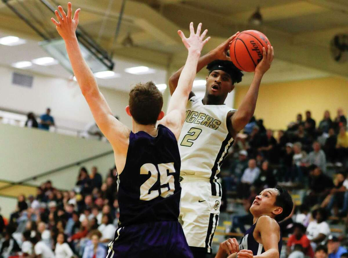 Conroe's Michael Phoenix II (2) makes a pass between Klein Cain's Ty Kisleghy (25) and Drey Ubas (0) during the fourth quarter of a District 15-6A high school basketball game at Conroe High School, Friday, Dec. 13, 2019, in Conroe.