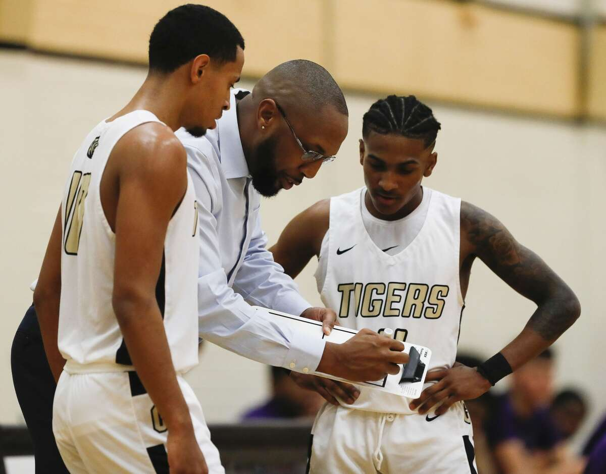 Conroe head coach Daryl Mason draws a plays with Conroe point guard Anthony Theragood (4) and shooting guard Isaac Wilkerson (10) during the third quarter of a District 15-6A high school basketball game at Conroe High School, Friday, Dec. 13, 2019, in Conroe.