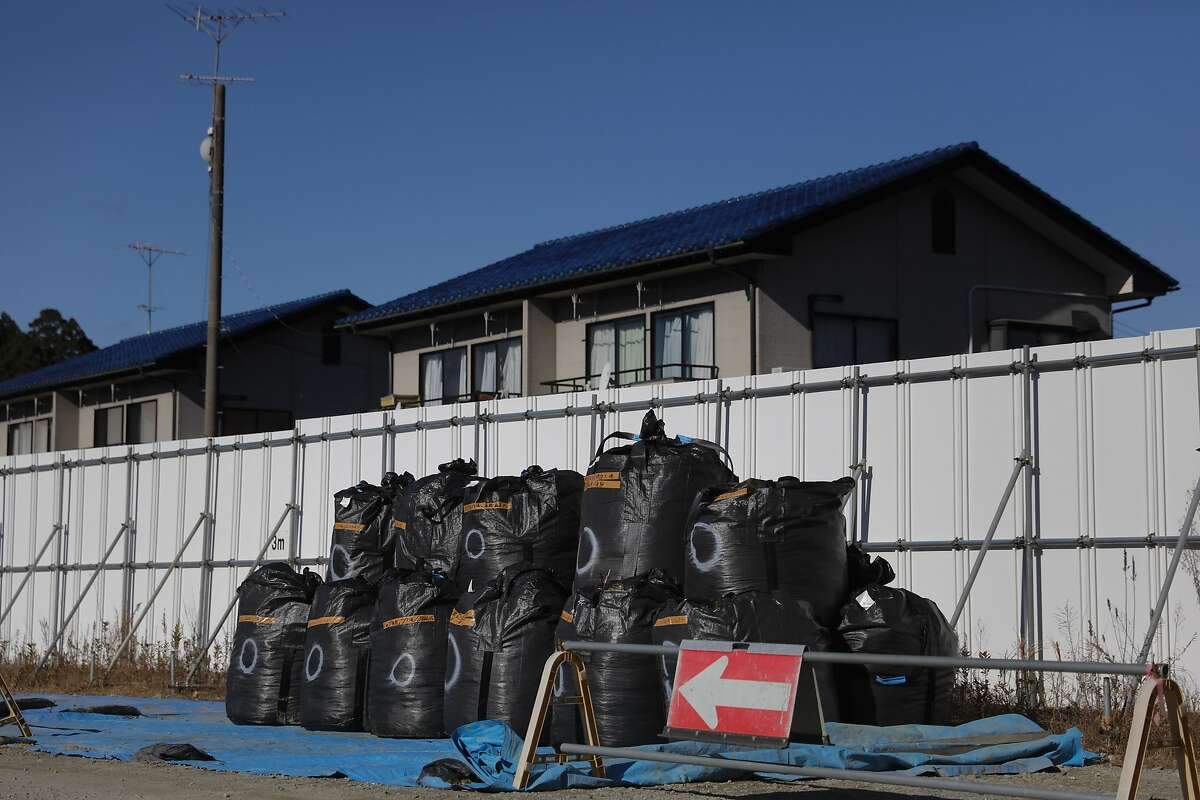 Large black plastic bags containing radioactive waste are stacked next to homes Tuesday, Dec. 3, 2019, in the abandoned town of Futaba, Fukushima prefecture, Japan. Government officials say it's