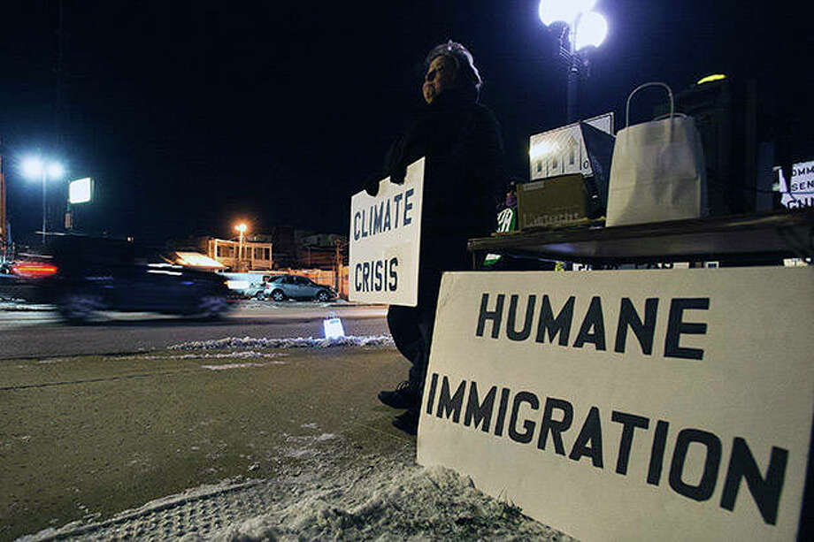 Sara Holthaus Weidemier of Normal stands along East Street in Bloomington during a vigil sponsored by Stand Up for Social Justice. Photo: Lewis Marien   The Pantagraph (AP)
