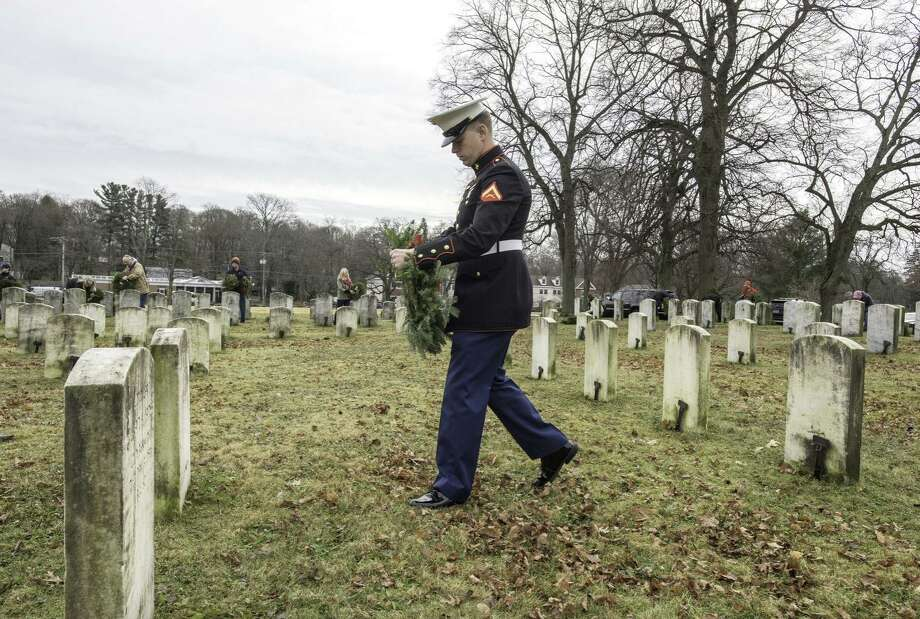 Lance Corporal Marine Christopher Schenarts lays a wreath on the grave of his great-great-uncle Arthur Schenarts.  This year's Wreaths Across America event will be on Saturday, Dec. 14 at noon. — at Spring Grove Cemetery Assoc. Photo: Laureen Vellante