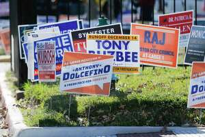 Political signs outside of Metropolitan Multi Service Center in Houston on Monday, Dec. 2, 2019, as voters make their way to the polls for early voting.