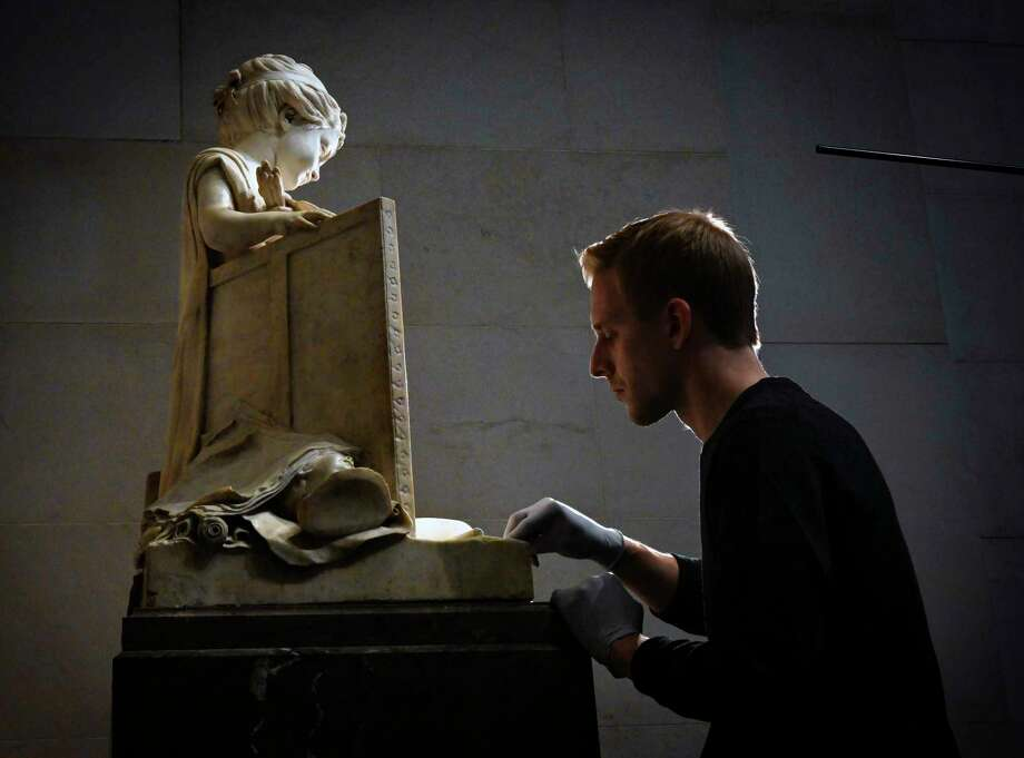 """Robert Price works on cleaning """"Painting and Sculpture"""" by Jean-Pierre-Antoine Tassaert, in the main hall of the National Gallery of Art. Photo: Washington Post Photo By Bill O'Leary / The Washington Post"""