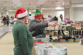 Individuals, with the help of local volunteers, shop for toys at the annual Toys for Tots distribution event on Saturday, Dec. 14 at the Midland Mall.