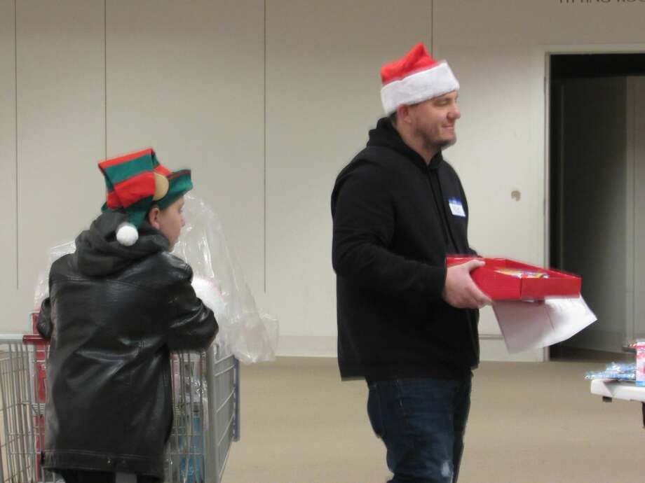 Individuals, with the help of local volunteers, shop for toys at the annual Toys for Tots distribution event on Saturday, Dec. 14 at the Midland Mall. Photo: Victoria Ritter/vritter@mdn.net