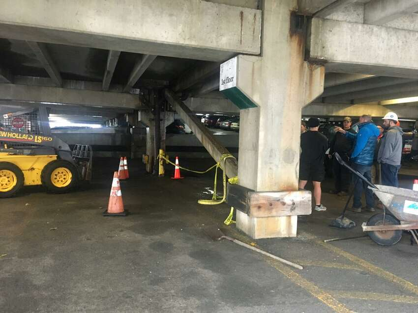 City officials and others respond after a beam fell inside the Uncle Sam Garage in Troy.