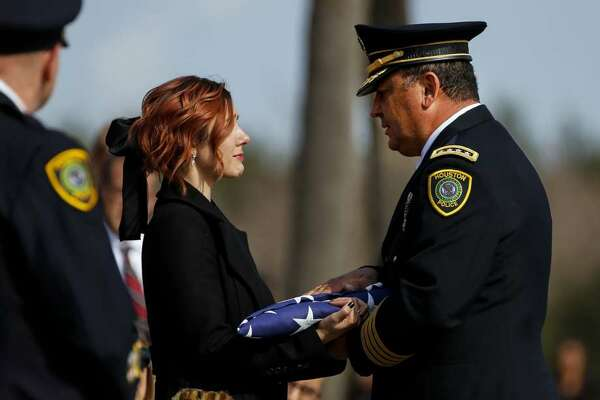 Houston Police Chief Art Acevedo presents a flag to Houston Police Sgt. Christopher Brewster's widow, Bethany Elise Brewster, during a funeral service Thursday, Dec. 12, 2019, at Grace Church Houston in Houston. Brewster, 32, was gunned down Saturday evening, Dec. 7, while responding to a domestic violence call in Magnolia Park. Police arrested 25-year-old Arturo Solis that night in the shooting death. Solis faces capital murder charges. (Godofredo A. Vasquez/Houston Chronicle via AP)