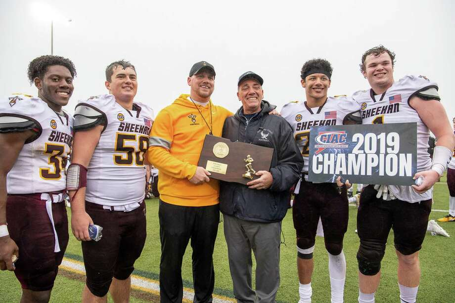 Sheehan Titans head coach John Ferrazzi accepts the 2019 CIAC Football Class S Championship plaque with Captains Shaine Salvador (34), Thomas DiPasquale (58), Jordan Davis (27) and Braedon McCarthy (1). Photo: David G. Whitham / For Hearst Connecticut Media / Stamford Advocate Freelance