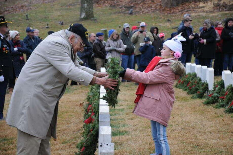 World War II veteran Arthur Williams and 10-year-old Birdie Elliott of Godfrey place wreaths in Alton National Cemetery on Saturday. Wreaths Across America placed wreaths Saturday at 530 tombstones at the cemetery.