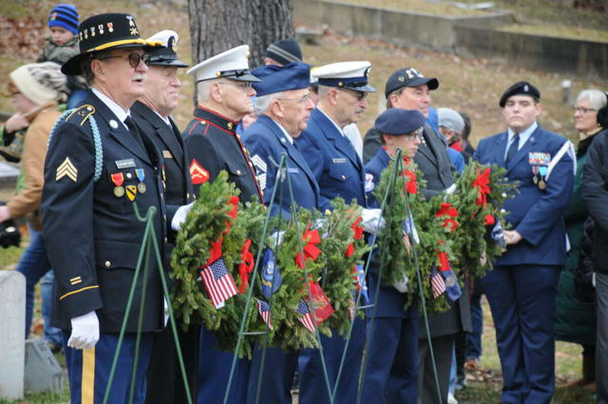 FILE - Veterans representing each branch of the U.S. military wait to place wreaths during a ceremony in Alton National Cemetery.