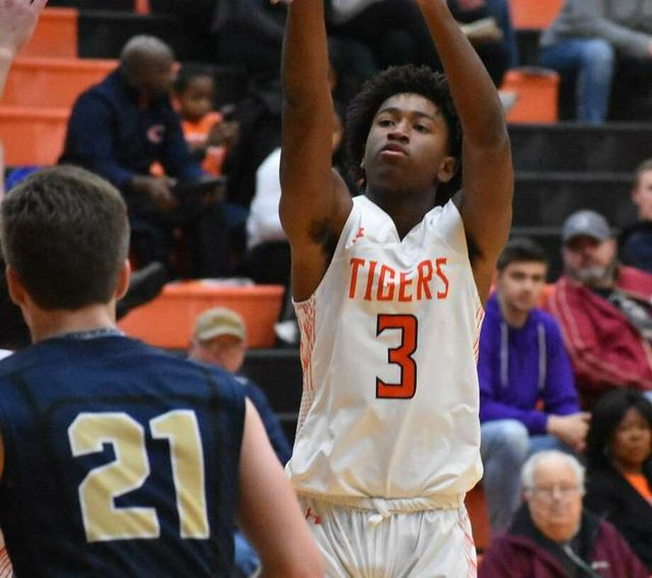Edwardsville guard Gabe James puts up a 3-point attempt over an Althoff defender in the second quarter on Saturday in the second game of the Scott Credit Union Shootout.