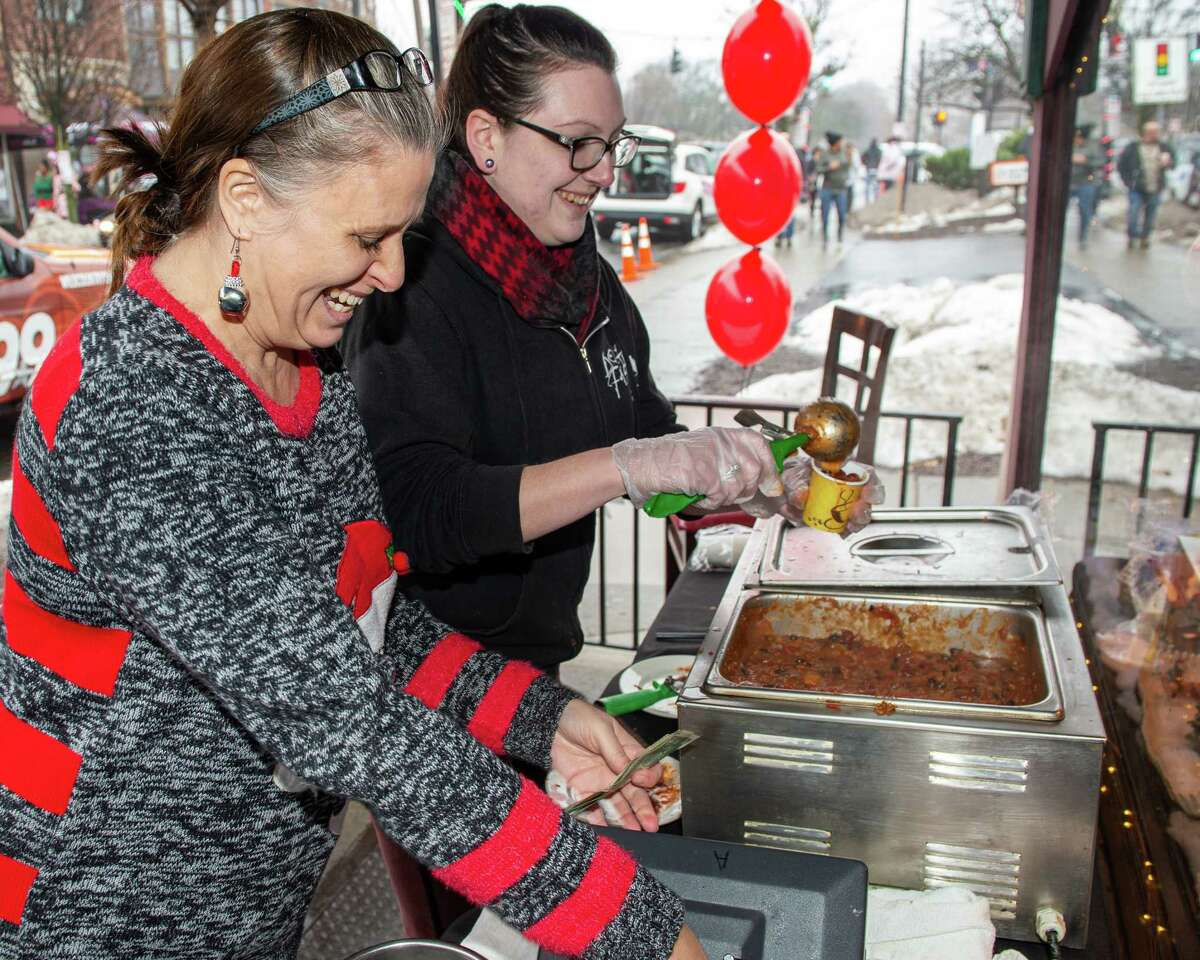 Jody Dater and Kay Pierce serve chili outside the Savoy Taproom during the 14th Annual Santa Speedo Sprint on Lark Street in Albany, New York, to benefit the Albany Damien Center and the HIV/AIDS program at Albany Medical Center Hospital on Saturday, Dec. 14, 2019 (Jim Franco/Special to the Times Union.)
