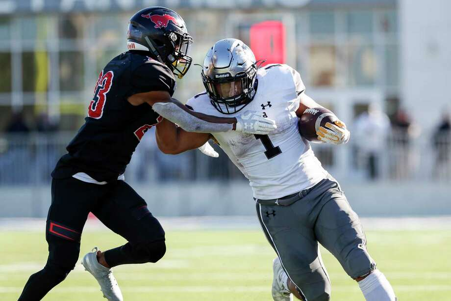 Denton Guyer Wildcats Kaedric Cobbs (1) runs for a first down defended by Westfield Mustangs Kayden Craig (23) during the second half of the high school football playoff game between the between the Denton Guyer Wildcats and the Westfield Mustangs at Sheldon ISD Panther Stadium in Houston, TX on Saturday, December 14, 2019.  The Wildcats defeated the Mustangs 35-17. Photo: Tim Warner, Contributor / ©Houston Chronicle