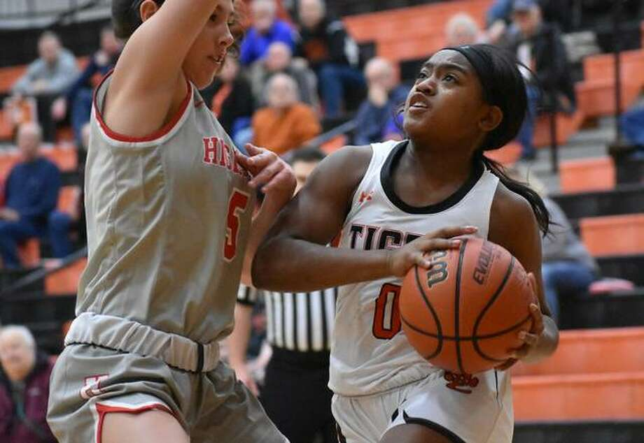 Edwardsville senior point guard Quierra Love drives to the basket against a Highland defender in the second quarter of Saturday's opening game of the Scott Credit Union Shootout.