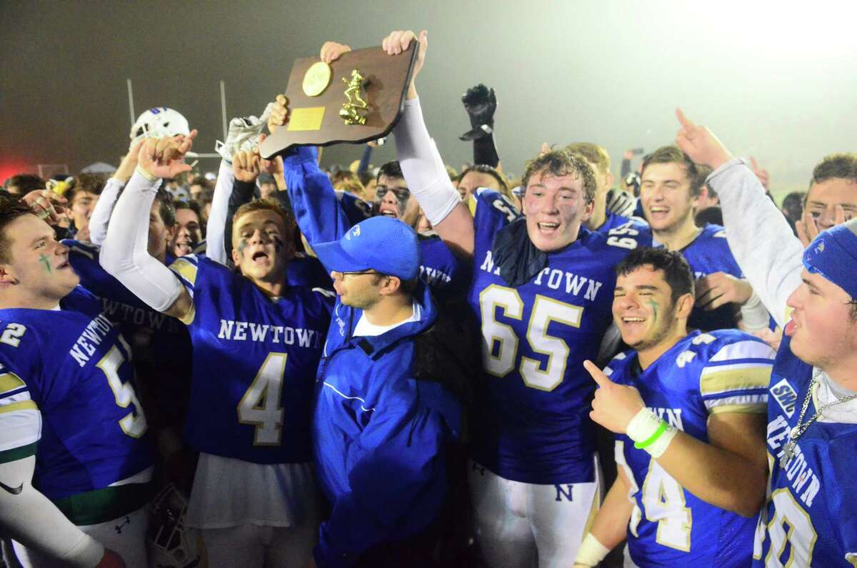 Newtown celebrates its win over Darien in the Class LL championship game Dec. 14.