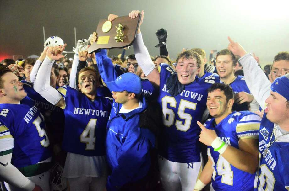 Newtown celebrates its win over Darien in the Class LL championship game Dec. 14. Photo: Christian Abraham / Hearst Connecticut Media / Connecticut Post